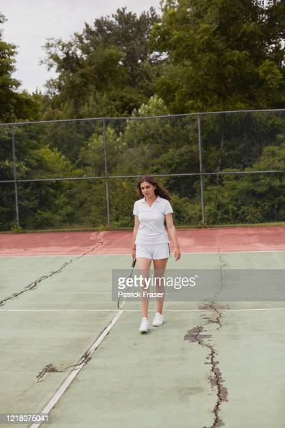 young female walking towards camera on hard tennis court holding a racket - racquet stock pictures, royalty-free photos & images
