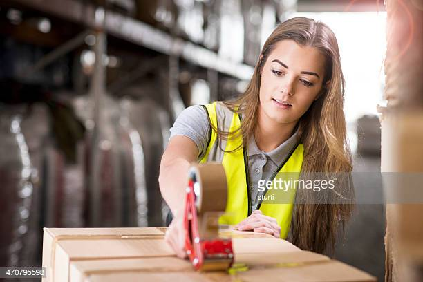 young female warehouse worker packing boxes for shipment - tape dispenser stock photos and pictures
