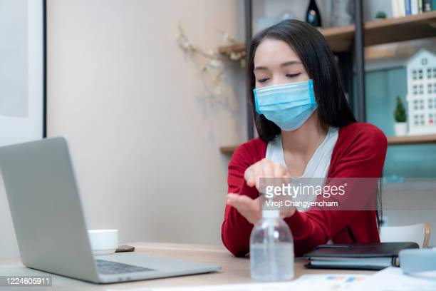 young female wear face protective mask taking care of hands hygiene before working, selective face focus - pump dress shoe stock pictures, royalty-free photos & images