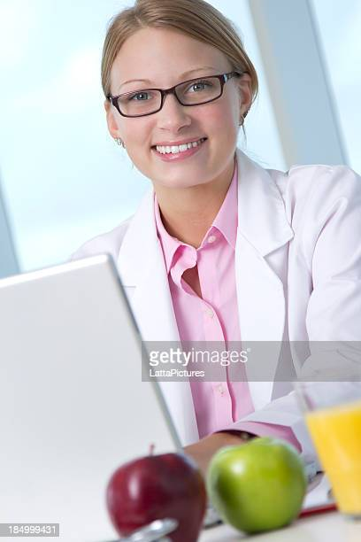 Young female wearing lab coat sitting at desk with laptop