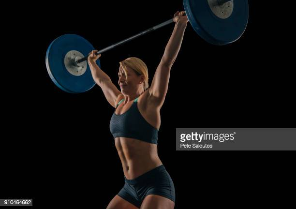 Young female weightlifter practicing barbell weightlifting snatch