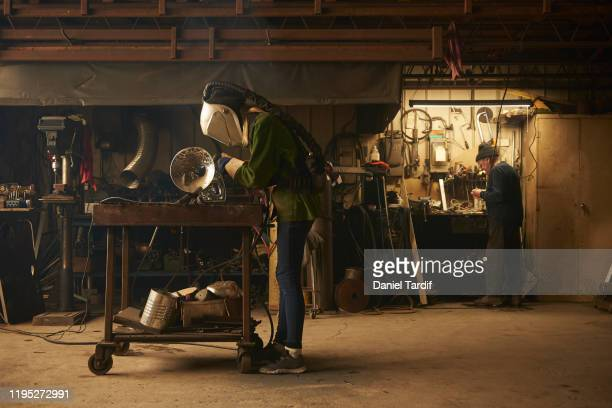 young female welder working in shop. - daniel funke stock-fotos und bilder