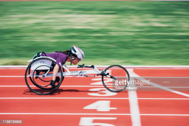 young female wheelchair racers crossing the finish line at a track and field event - athletics stock pictures, royalty-free photos & images