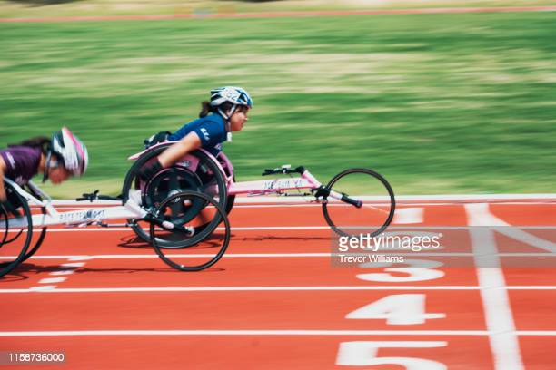 young female wheelchair racers crossing the finish line at a track and field event - 障害者スポーツ ストックフォトと画像