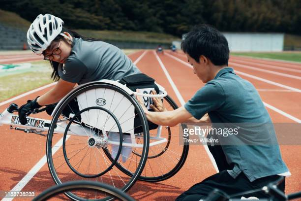 young female wheelchair racers prepare for a competition with the support of their parent or coach - athlete stock pictures, royalty-free photos & images