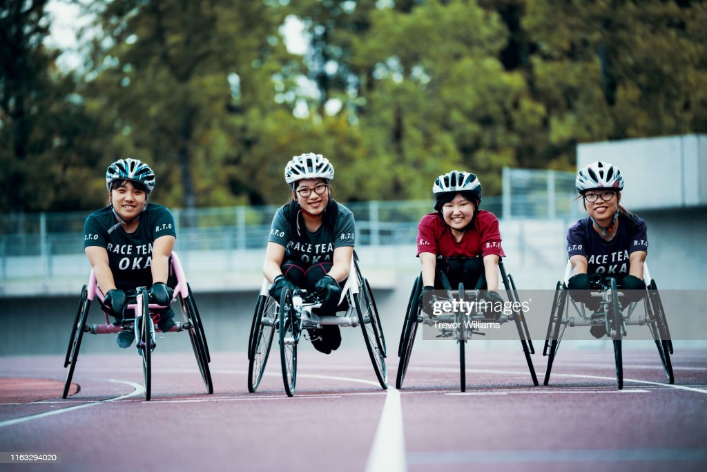 Young female wheelchair racers prepare for competition at a track and field event : ストックフォト