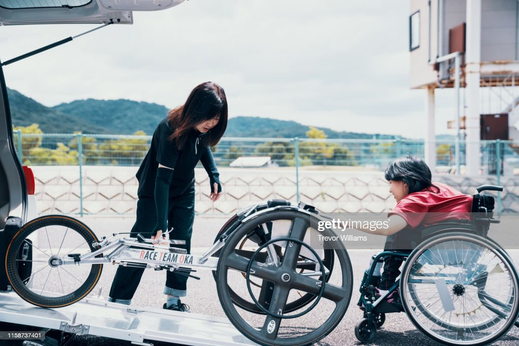 Young female wheelchair racerunloading her racing wheelchair from a car : ストックフォト