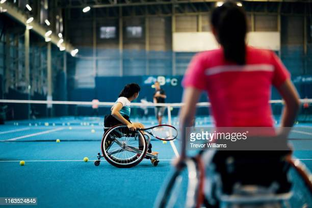 young female wheelchair tennis players practice together with their coach at an indoor tennis court - ラケット ストックフォトと画像