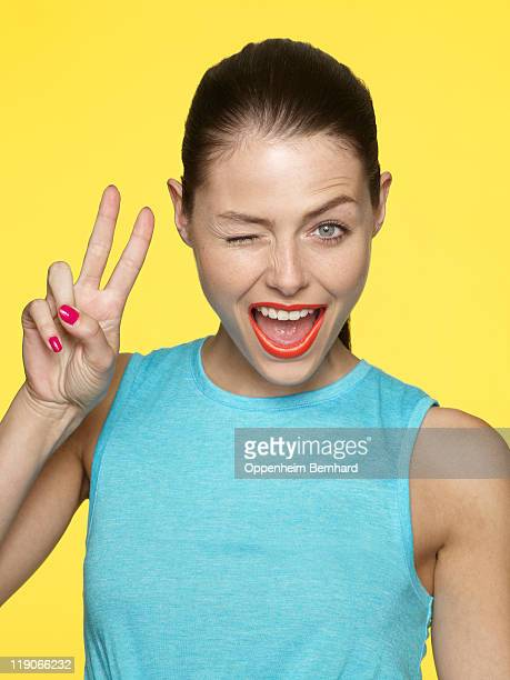 young female winking and creating peace sign