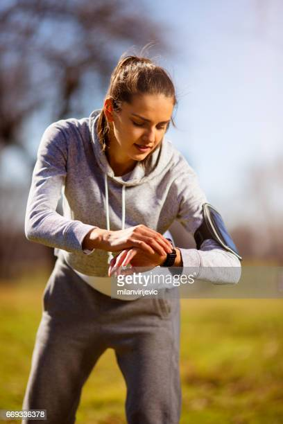 Young female with watching in stopwatch for running