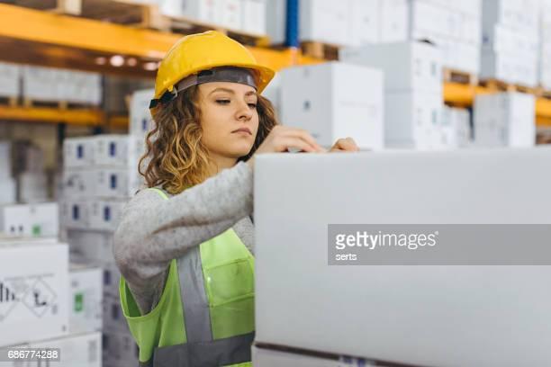 Junge Arbeitnehmerin Check-Boxen für den Transport im Lager