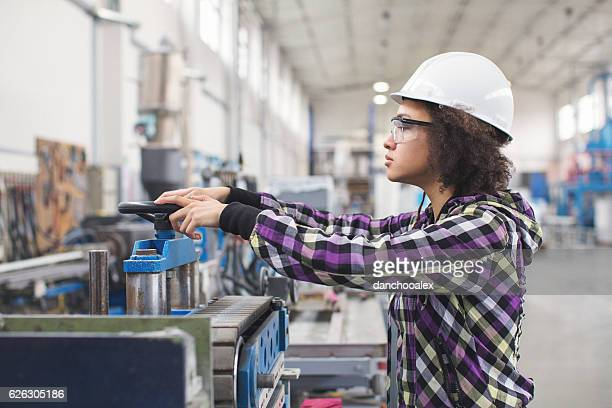 Young female worker operating a machine in factory
