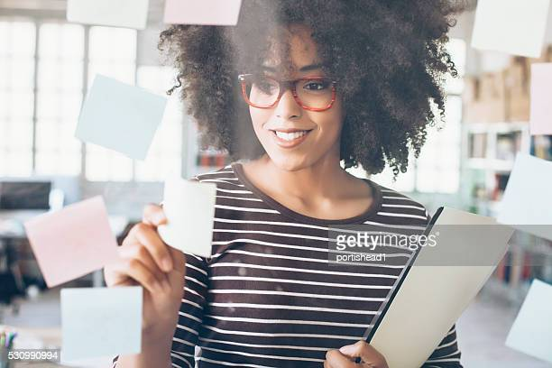Young female worker taking sticky notes from window