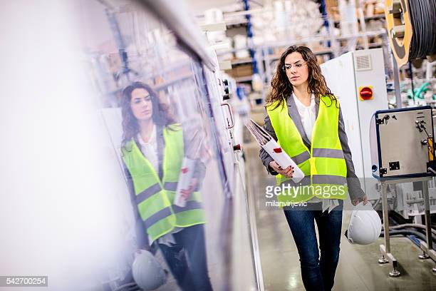 young female worker walking through the factory - weibliche angestellte stock-fotos und bilder