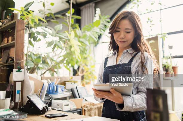 young female worker working in flower shop. - happy merchant stock pictures, royalty-free photos & images