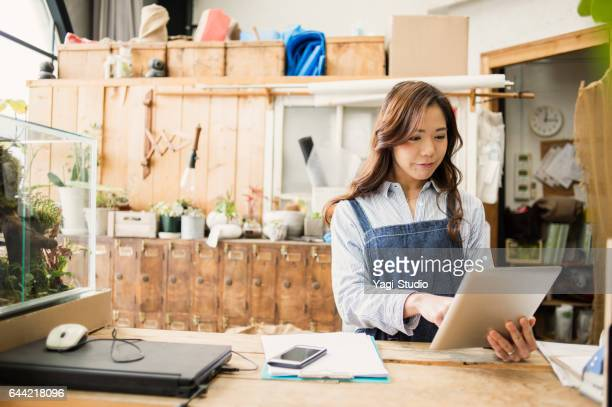 Young female worker working in flower shop.