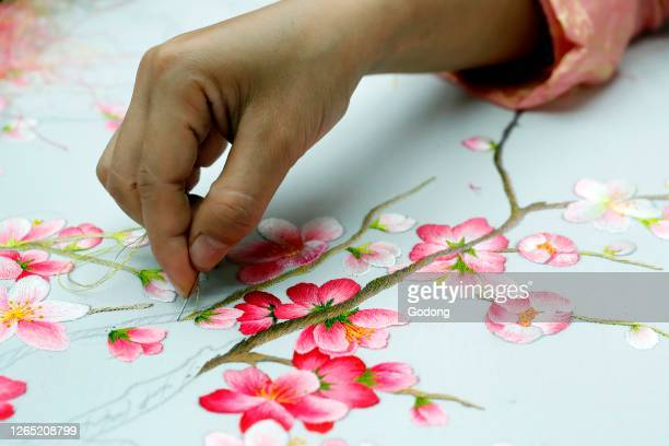 Young female workers doing embroidery. Flowers. Close-up on hand. Hue. Vietnam.