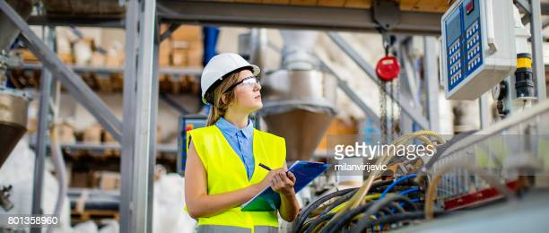 Young female working in factory as quality controller