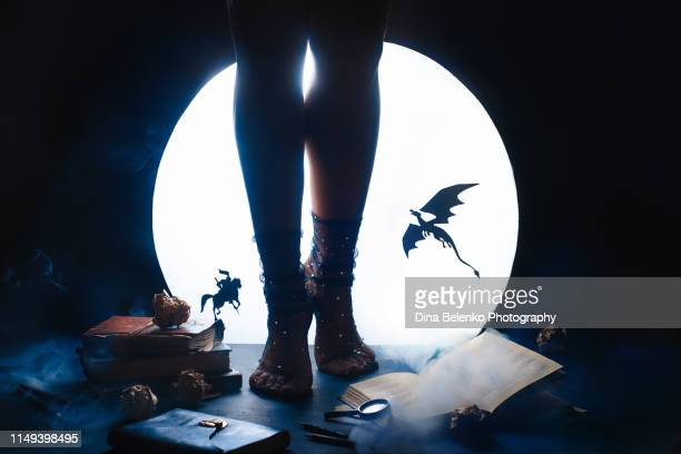 a young female writer with a fairy tale book. dragon and knight silhouettes against shiny moon background. legs in starry socks - fictional character stock pictures, royalty-free photos & images