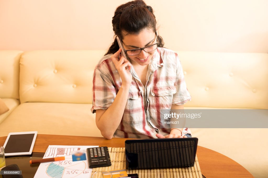 Young female writing notes while talking on phone : Stock Photo