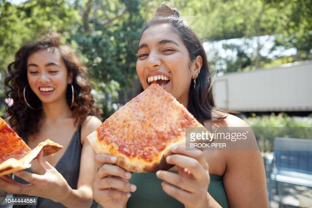 Young females hanging out in city eating pizza