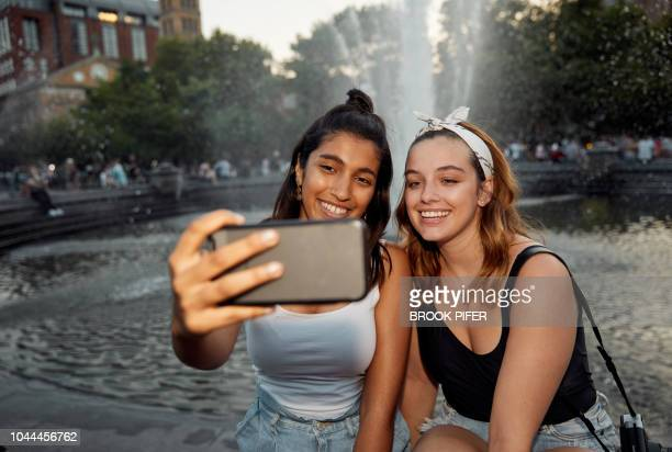 Young females hanging out on city park water fountain taking selfie