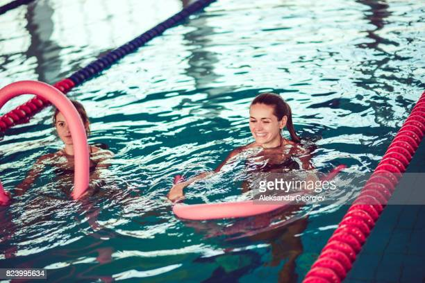 Young Females in Water Aerobics Class at Indoor Swimming Pool