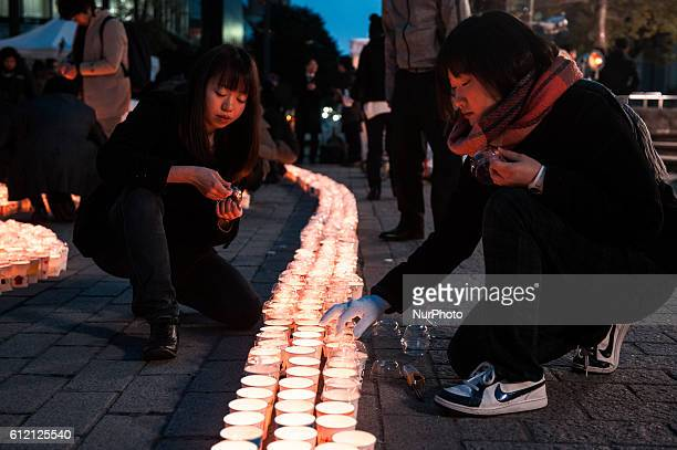 Young females light candles to pray for victims of massive earthquake and tsunami disaster during a memorial ceremony in Sendai Miyagi prefecture...