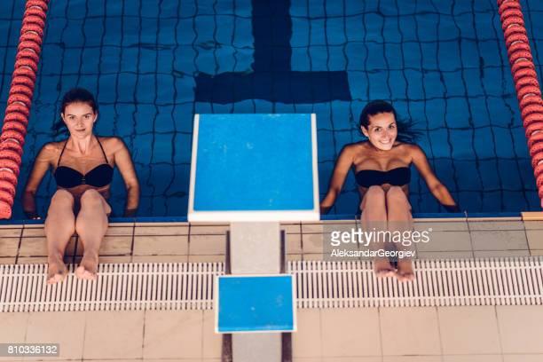 Hembras jóvenes descansando después de la clase de aeróbicos de agua en piscina cubierta
