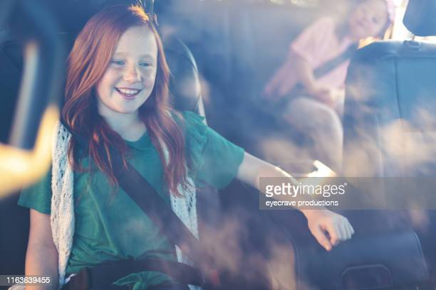 Young Females strapped in safety belts in automobile looking at camera