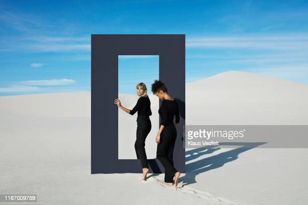 Young females walking through door frame at desert