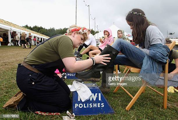 A young festival goer has her Wellington Boots cleaned and polished during Day 2 of the Vintage at Goodwood Festival on August 14 2010 in Chichester...