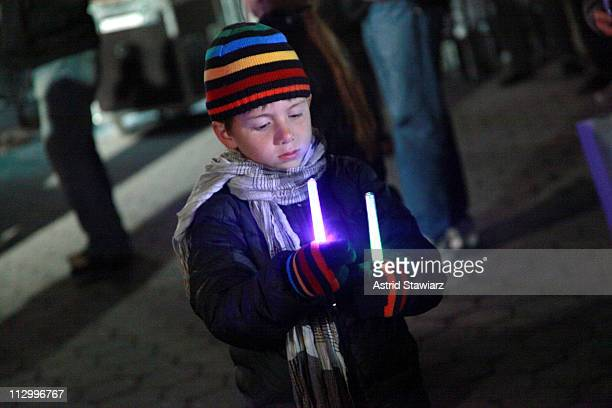 A young festivalgoer plays with glow sticks at a screening of 'When The Drum Is Beating' during the 2011 Tribeca Film Festival at North Cove at World...