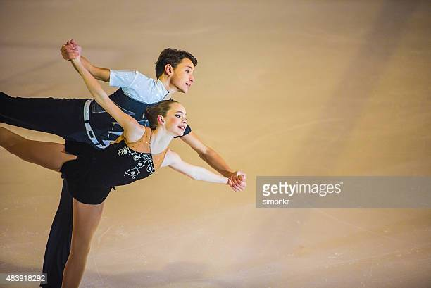 Young figure skating pair performing