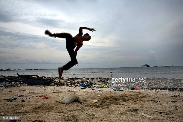 A young filipino boy flips through the air on the polluted beach of Baseco Tondo district in Manila Philippines on August 7 2008 Photo by Lisa Wiltse