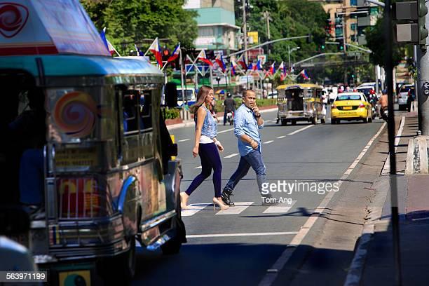 young filipino cross busy street, manila - マニラ ストックフォトと画像