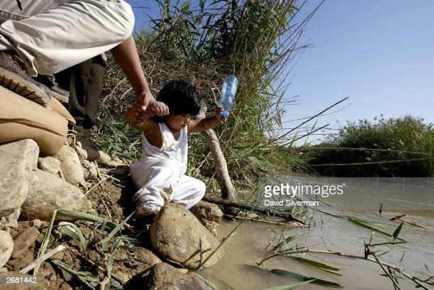 A young Filipino girl holds tight to her mother's hand as she collects holy water from the Jordan river October 30 2003 at Qasr alYehud in the West...
