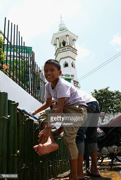 Young Filipino Muslim children washes their feet as they attend noon prayer at the Mosque ahead of the celebrations for Eid ul-Fitr on September 18,...