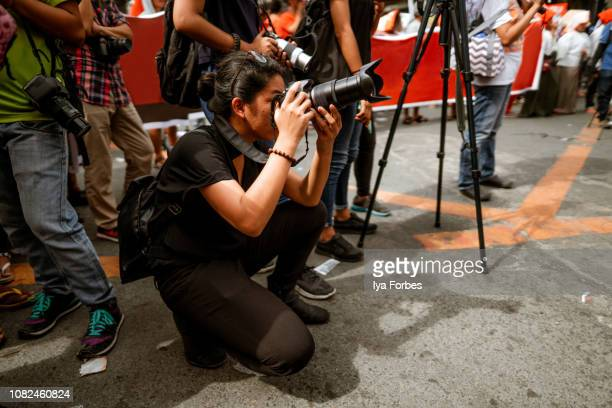 young filipino student photojournalist taking photographs - photojournalist stock pictures, royalty-free photos & images