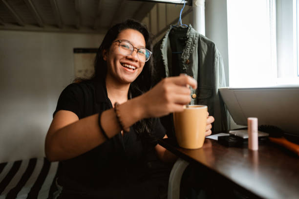 Young Filipino woman making coffee in her college dorm room