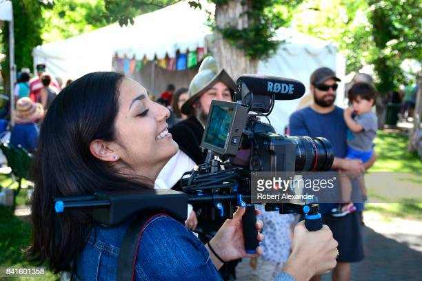 Young film and video college student videotapes an interview at the annual Spanish Market festivities in Santa Fe, New Mexico. The summer event...