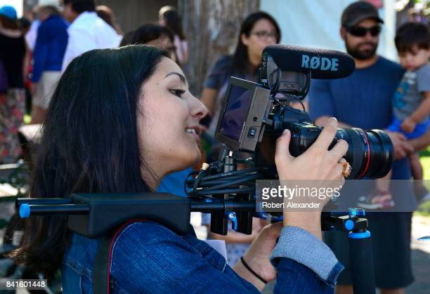 A young film and video college student videotapes an interview at the annual Spanish Market festivities in Santa Fe New Mexico The summer event...