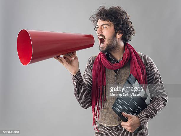 young film director shouting through megaphone - film director stock pictures, royalty-free photos & images