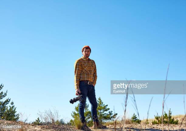 a young filmmaker standing in dunes and high grass holding a small camera, looking into camera. - アウトドア ストックフォトと画像