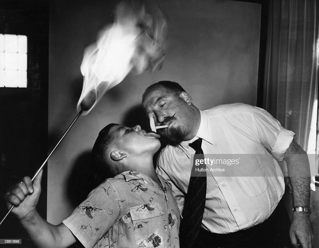 A young fire-eater gives his father a light from his tongue.