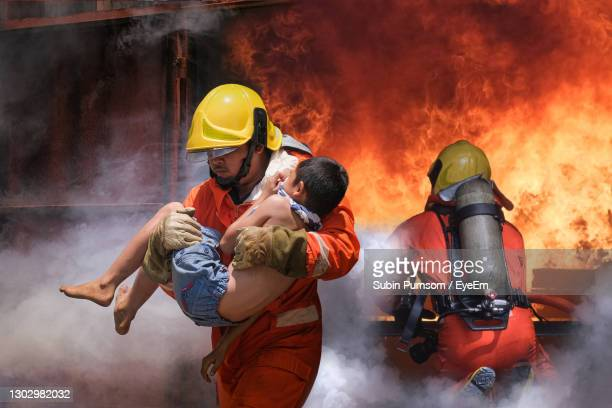 young firefighter saving boy from fire - rescue stock pictures, royalty-free photos & images