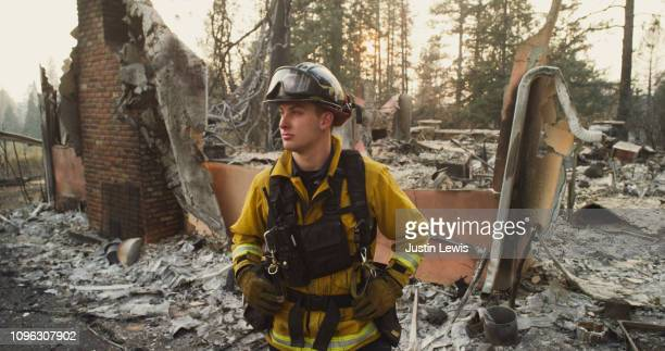 Young Firefighter Stands With Eerie Smoke-Filtered Sunlight Illuminating His Face, Surrounded by Houses Destroyed in the Paradise Wildfire 2018