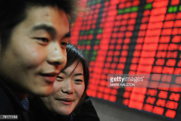Young first time investors smile in front of a stock price board showing the red colouring which indicates rising prices at a private securities firm...