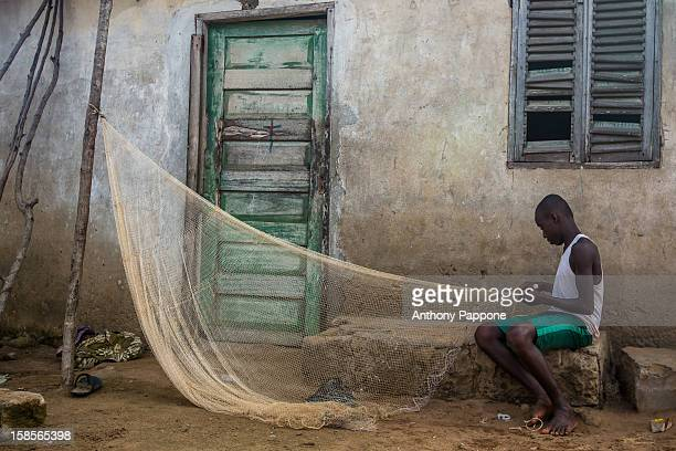Young fisherman adjusts his fishing net, a village on the coast of Ghana