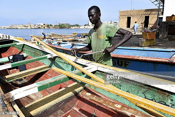 A young fisherman fixes a wooden pirogue at the traditional fishing harbour of Soumbedioune in Dakar on July 2 2015 The fishermen's colourful...